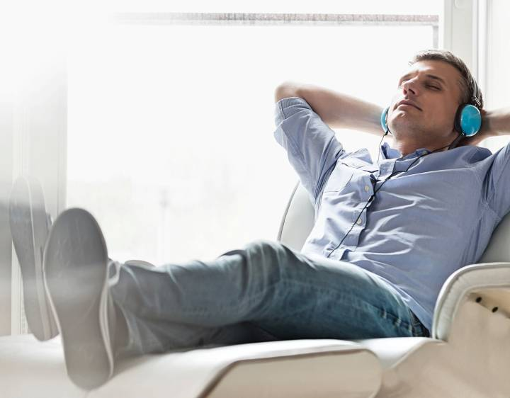 A man listening to music in a heated recliner