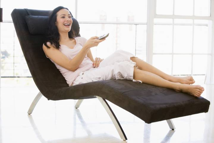 A woman changing TV channels in a heated recliner